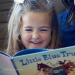 Little girl reading the Little Blue Truck book.